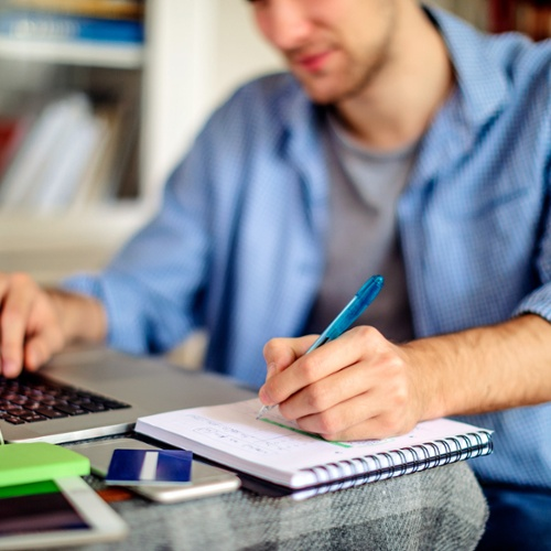business management online degree completion white male student takes notes while using his laptop