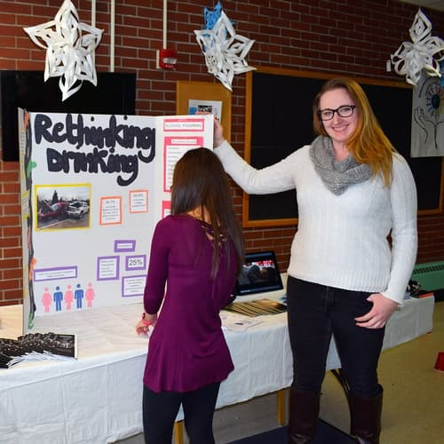 two female behavioral science students setting up a display in Cyr Hall
