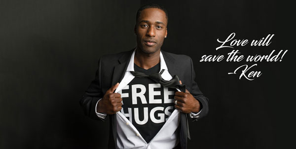 "Motivational Spealer Ken E. Nwadike, Jr. wearing a t-shirt under his suit that reads, ""free hugs."""