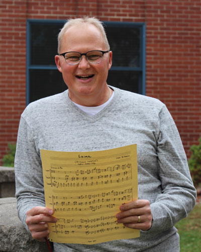 Dr. Scott Brickman stands outside, holding sheet music of one of his compositions.
