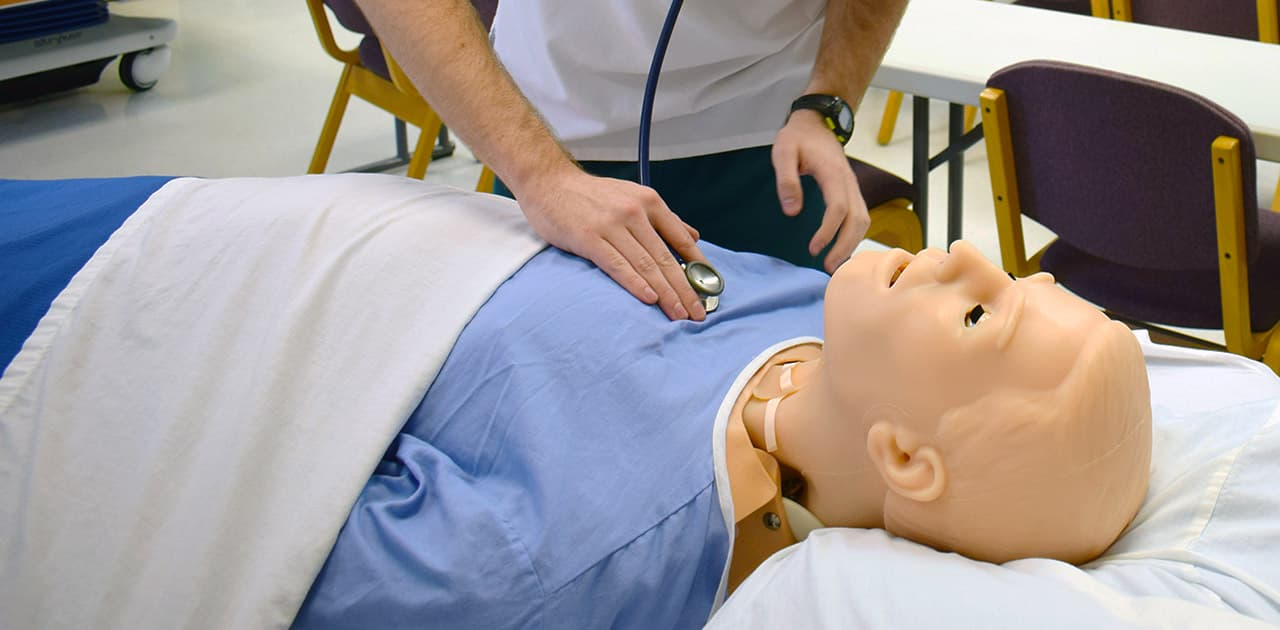 a student practices listening to a patient's lungs using a practice mannequin