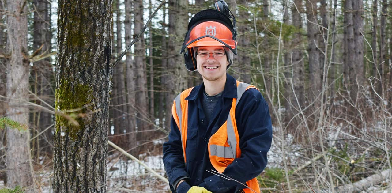 forestry student Alex Gillis stands in a forest wearing forestry safety gear