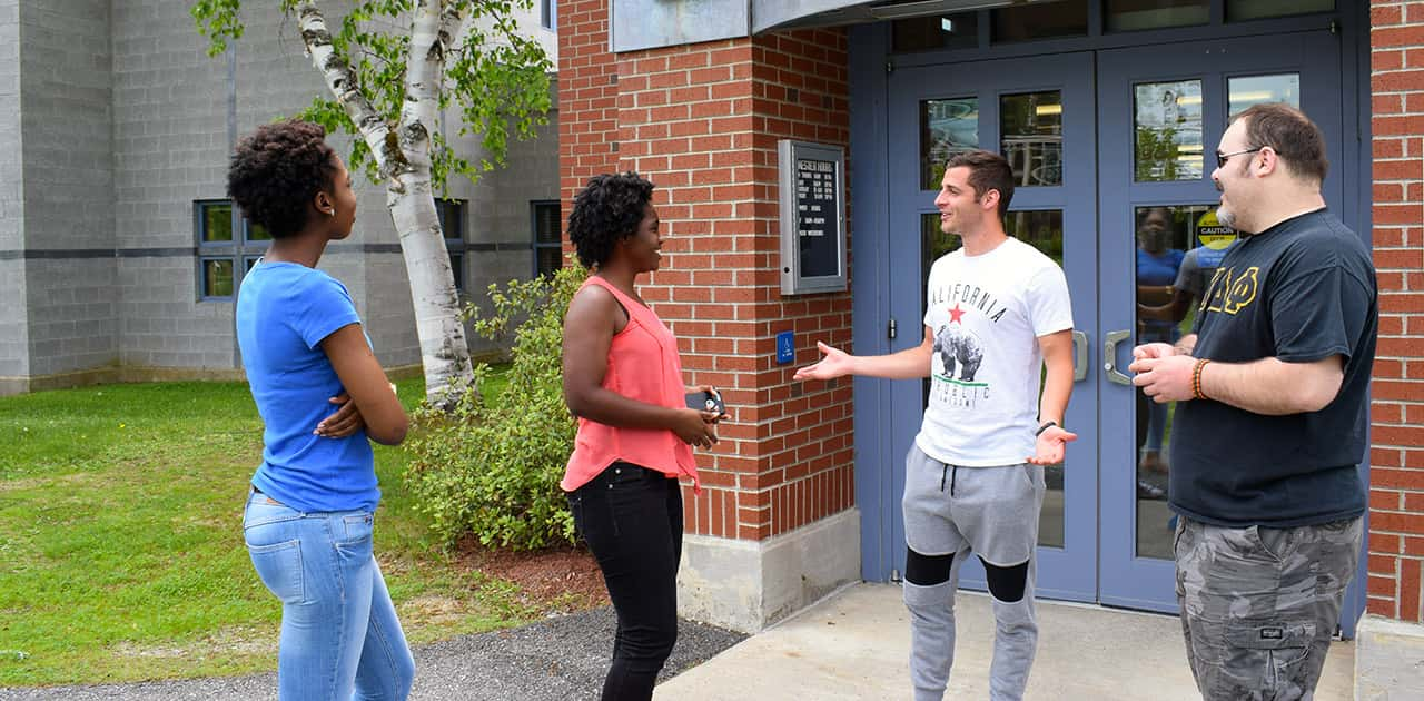 a group of UMFK students talk while standing outside of Blake Library