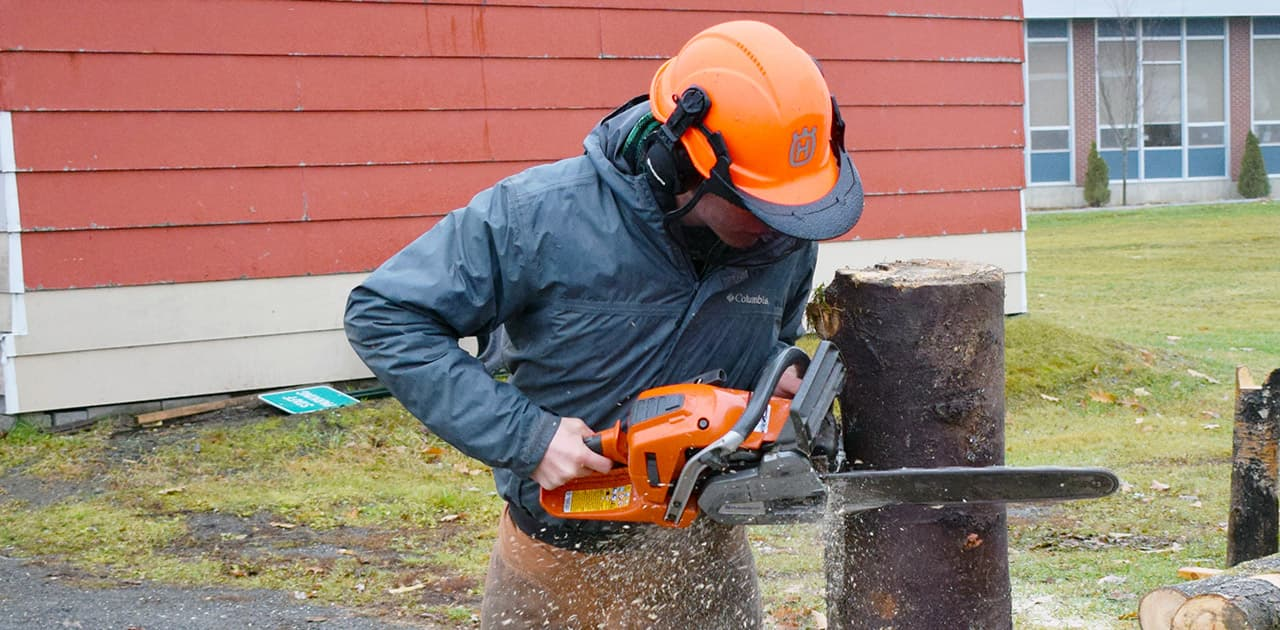 UMFK forestry student uses a chainsaw to cut a stump