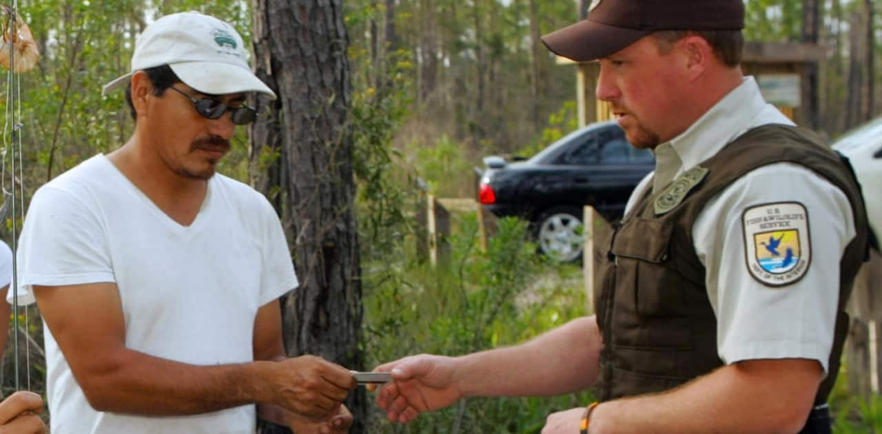 a fish and wildlife officer reviews the fishing licenses of a group of people