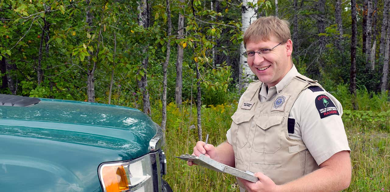 a UMFK graduate working as a forest ranger poses in uniform with clipboard in hand