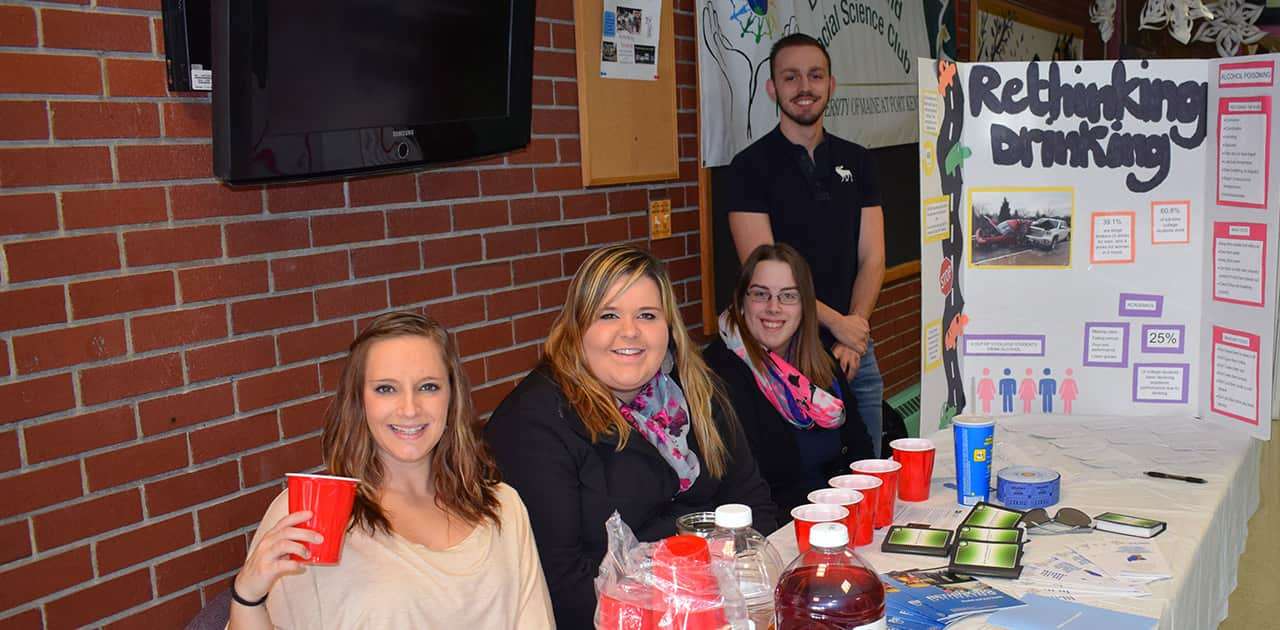 behavioral studies students sit outside the Bengal's Lair near a display on rethinking drinking