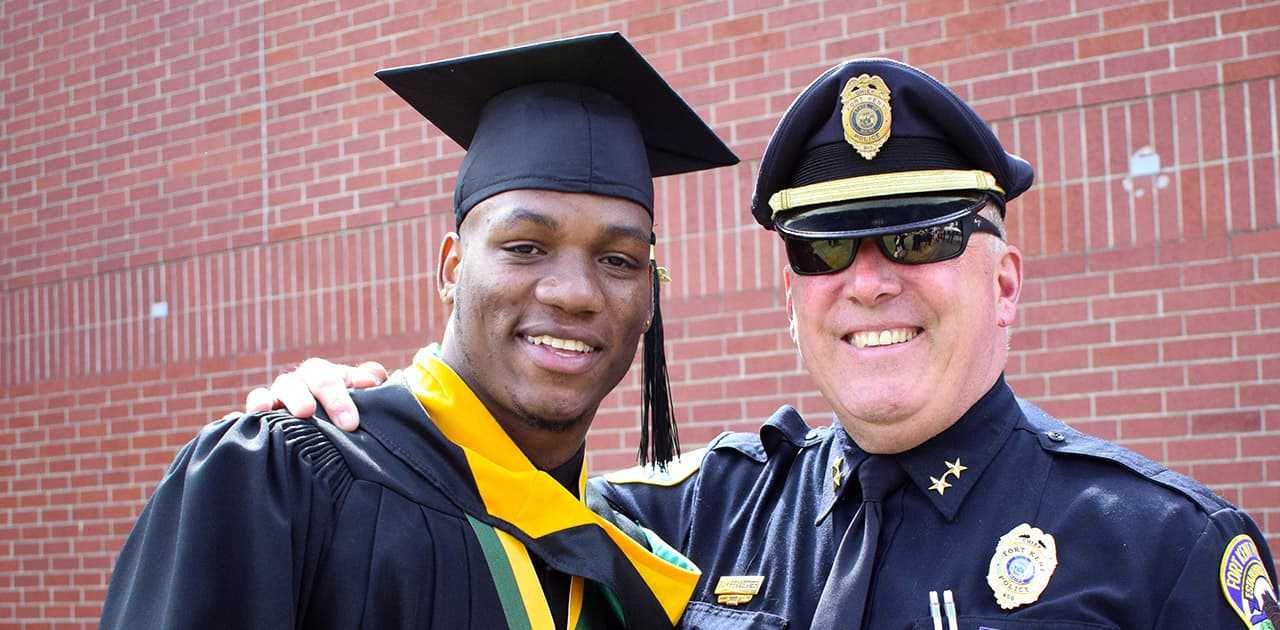 UMFK graduate posing with a local police officer shortly after commencement exercises