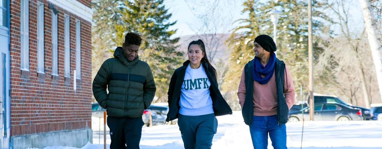 three umfk students walking outdoors in the middle of winter