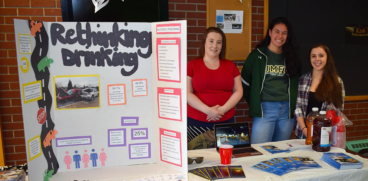 members of the behavioral science club stand next to a table presenting a display on rethinking drinking