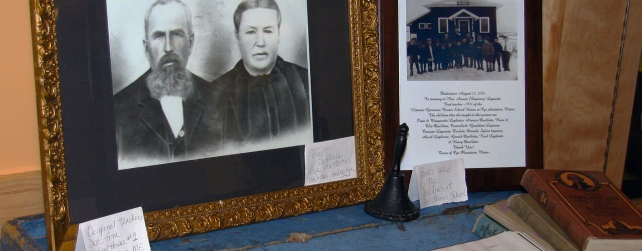 photo, drawing, books, and hand-held school bell on display during the Beatrice Craig exhibit at the Acadian Archives